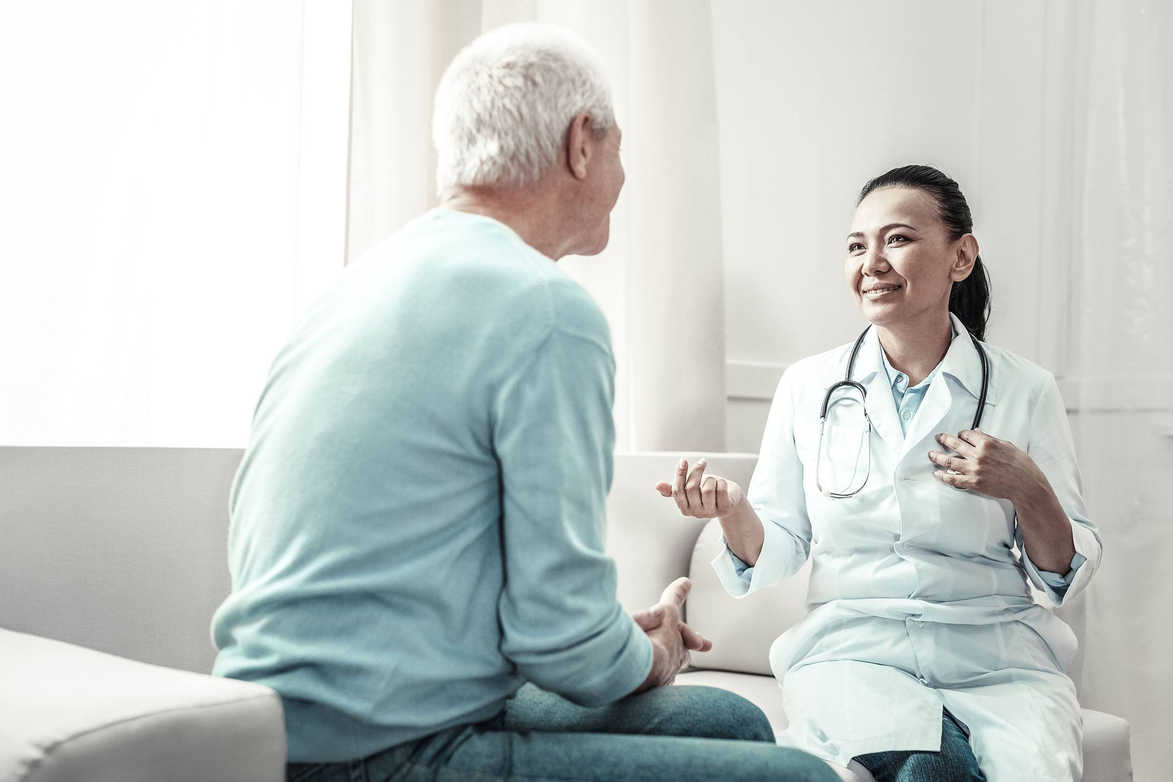 Female doctor talking to elderly patient in office